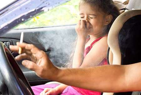 Child sitting in car with parent smoking