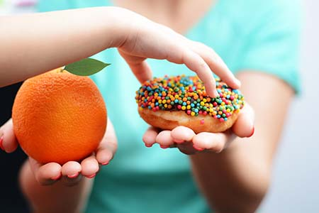 one hand grabbing donut while other holds orange