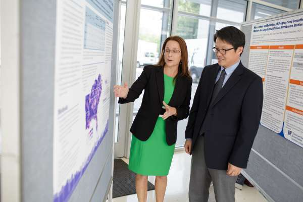Researchers discuss data at poster session.