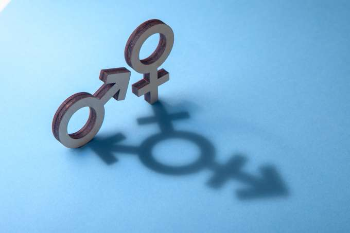 Symbols of man and woman cast shadow in the form of transgender on blue